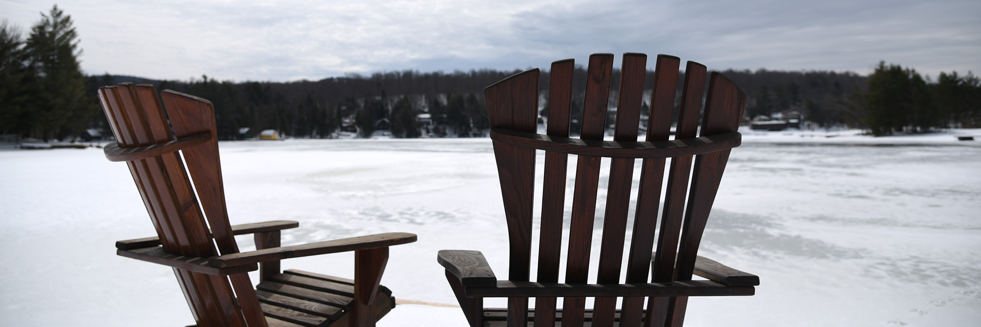 Experience Old Forge. Winter photo of Adirondack chairs on the lake.