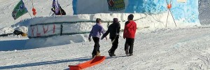 Kids dragging a sled up a hill next to a massive snow fort