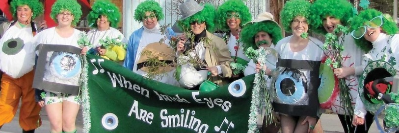 People in a line smiling with green wigs and st Patricks day items holding a green banner that say when Irish eyes are smiling