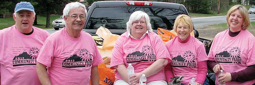 Five citizens on the back oof a truck and standing wearing matching pink community pride tee shirts