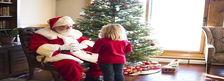 Santa sitting next to a Christmas tree with a little girl standing in front of him