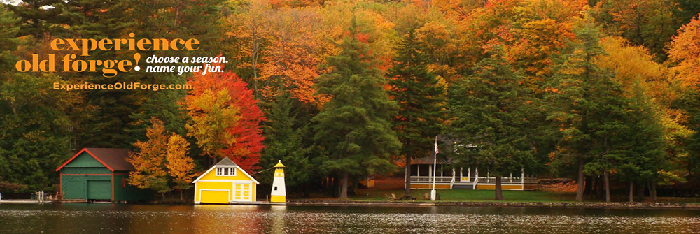the lake infant of a house with a barn and a dock with fall trees surrounding it and experience old forge choose a season name you fun experienceoldforge.com written over the image
