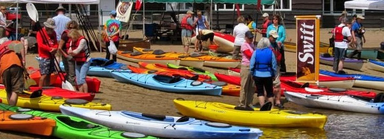 A big group of canoes on the beach and touching the water with people around them and a cabin in the background