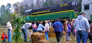 the Adirondack trail with family in from of it looking at hay bails pumpkins and cornstalks
