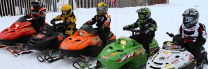 5 snowmobilers lined up on snowmobiles with their gear on