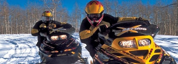 Two snowmobilers on a trail facing the camera
