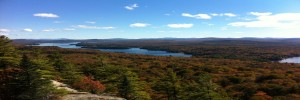 A view from the top of a mountain of fall foliage and calm clear lakes
