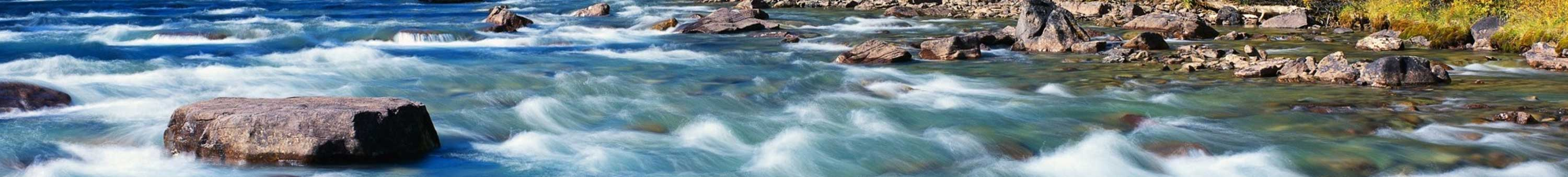 A rapid stream with rocks within and on the outer banks