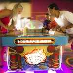 Two adults playing arcade games against themselves and kids watching them