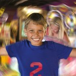 A kid smiling and holding a lot of tickets with everything around him blurred