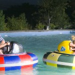a dad and son on one bumper boat squirting a mom and daughter on the other bumper boat while laughing