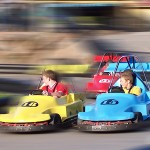 Kids racing on go karts with everything around them blurred