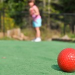 A picture of a red gold ball on a mini golf course and a woman in the blurred background