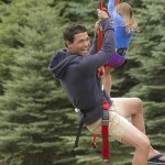 A man laughing on a zip line and a girl on the biplane behind him