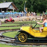 A little girl driving a car on tracks with parent and their kids int he background