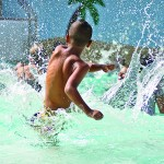 A kid splashing in a pool with a bunch of people smiling around him