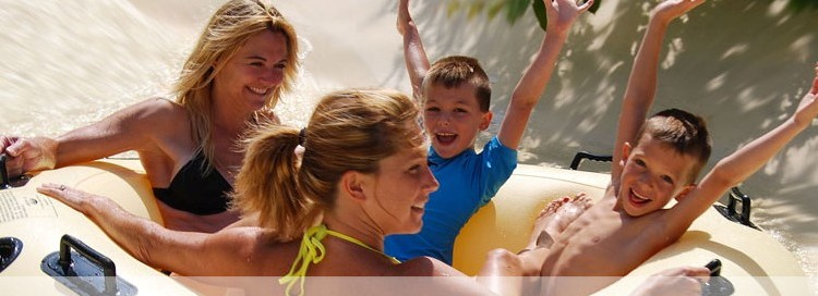Two women with two little boys smiling the boys have their hands in the air and they are going down a water slide