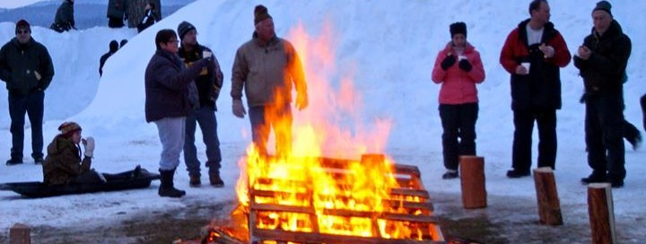 People standing around a campfire in winter in their snowier drinking hot beverages