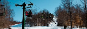 A ski lift with riders going up the mountain in winter