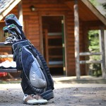 A cabin in the background with golf clubs leaning against a picnic table and gold shoes sitting around the clubs in the front of the image