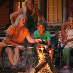 A family and smiling while roasting marshmallows over a campfire with a cabin in the background