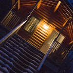 A log cabin at night in the win per with snow on the front step and it is snowing int he image