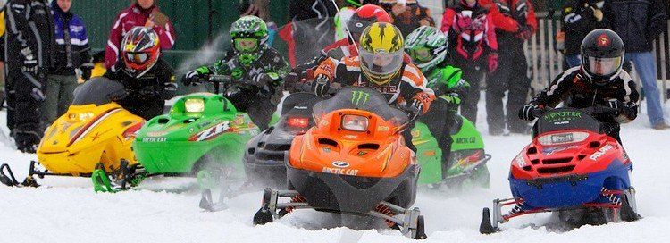 Snowmobilers racing with people standing in the background