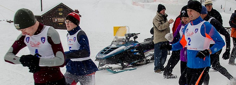 People dressed in racing gear running in the winter past a cabin and a snowmobile