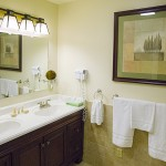 A bathroom with a double white sink and a bar with white hand towel and a nice picture hanging above it