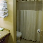 A bathroom with a white toilet, a bathtub with a shower curtain, a sink, and towels neatly stacked on a shelf next to the sink
