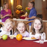 Kids smiling at the breakfast table with their food in front of them and two adults taking in front of the buffet behind the children